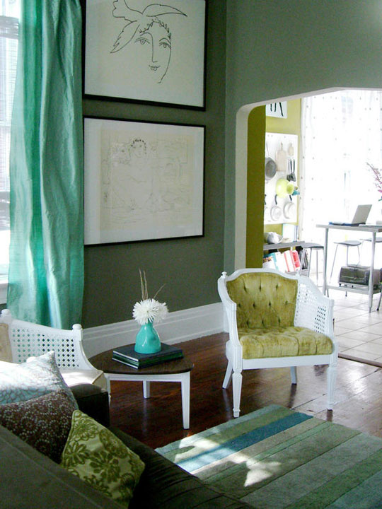 Green living room with comfy green sofa, white wooden chair with light green seat and back pad, green rug and dark wooden floors