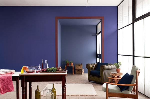 Dark purple wall colour in a modern living room with leather arm chair and dark wood table