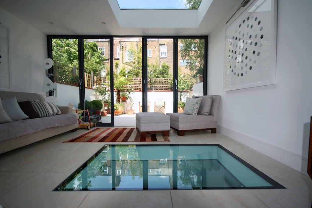 A solid glass floor inside a conservatory play room that has opening doors out to the garden