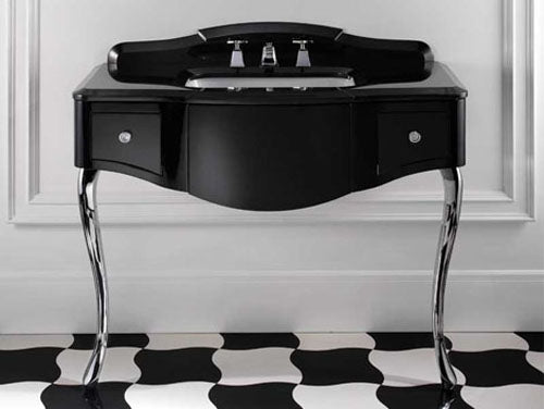 A black unit, containing a white sink, stood on black and white tiles