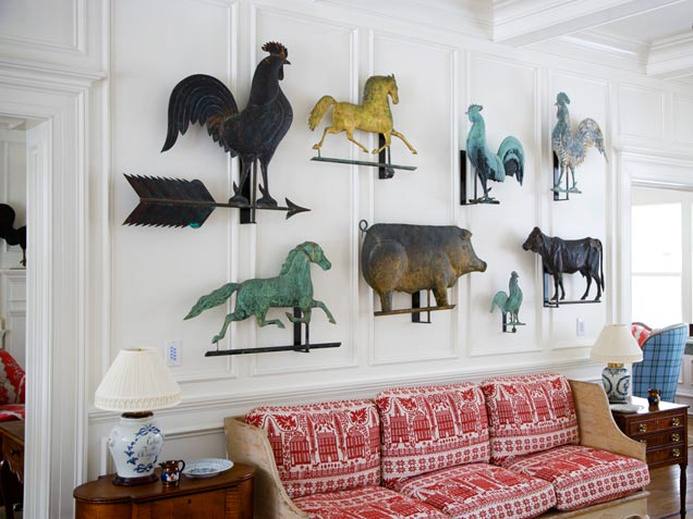 Different animal themed weather vanes hung on a white living room wall, including cockerel, horse, pig and cow