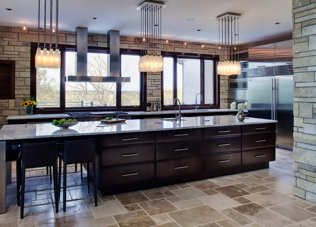 A long kitchen island with black unit drawers on the sides and mirror shine glass work surface on top
