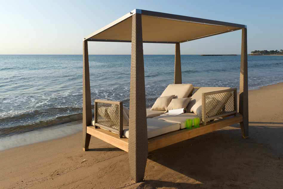 Four poster wooden day bed on the beach, next to the sea