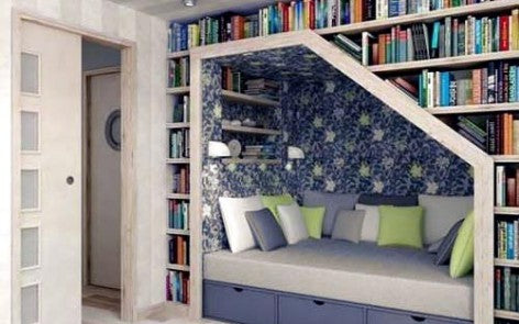 Blue and green reading nook surrounded at the sides and above by books and bookcases