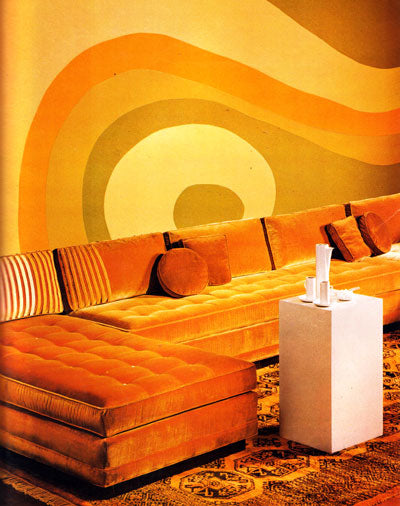 Orange psychedelic living space with swirling orange wall art and long orange corner sofa
