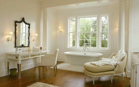 Luxury cream bathroom with white curved bathtub, dressing table and chaise lounge
