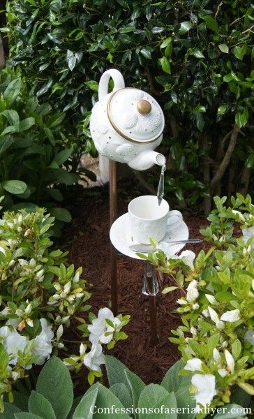 White ceramic teapot and teacup water feature, with water pouring into the cup