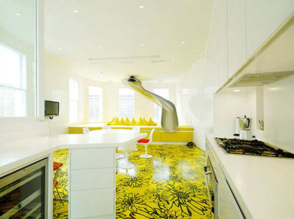 White and yellow kitchen with metal tube slide coming out of the ceiling