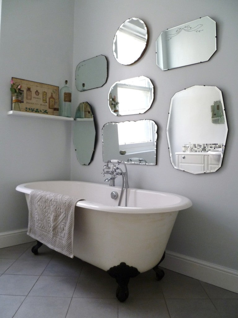 Different sized and shaped mirrors hung in a light grey bathroom above a white bathtub