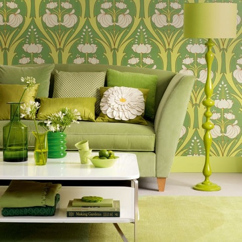 Very green living room with green wallpaper, sofa, cushions, lamp and coffee table accessories