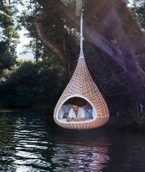 Suspended cocoon day bed, hanging over a river