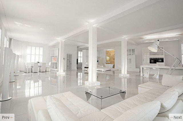 Large open plan white living space with four support columns in white, white sofas, white dining table and white bedroom