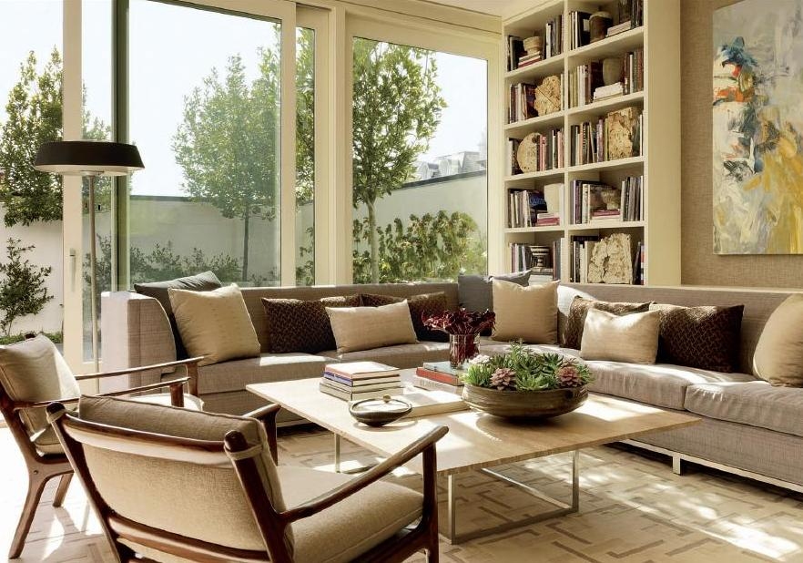 Cream and beige live room with beige corner sofa, square coffee table in light wood, cream shelves and sliding doors opening out to the garden
