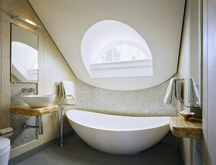 Cream bathroom with a sloping roof, white curved tub and arched window