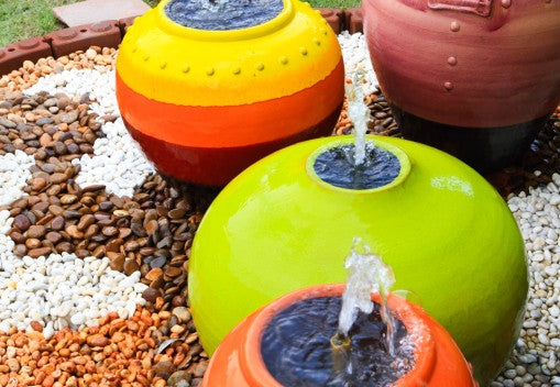 Brightly coloured pots in green, orange and yellow with water trickling out of them from the top