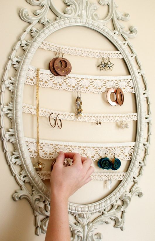 An ornate cream oval frame with no mirror or picture, but instead jewellery is hung inside it on rows of doily material