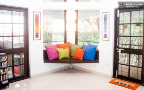 A corner window seat made of dark wood and covered in orange, yellow, pink and blue cushions