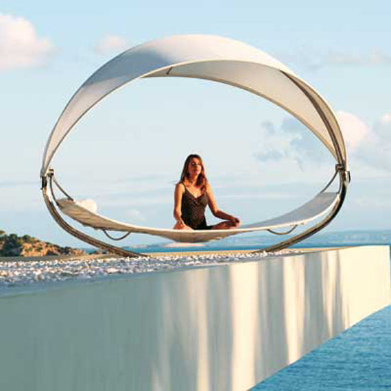 Woman meditating on a round metal framed day bed