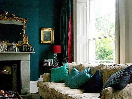 Dark emerald green living room, with beige sofa and green and blue cushions