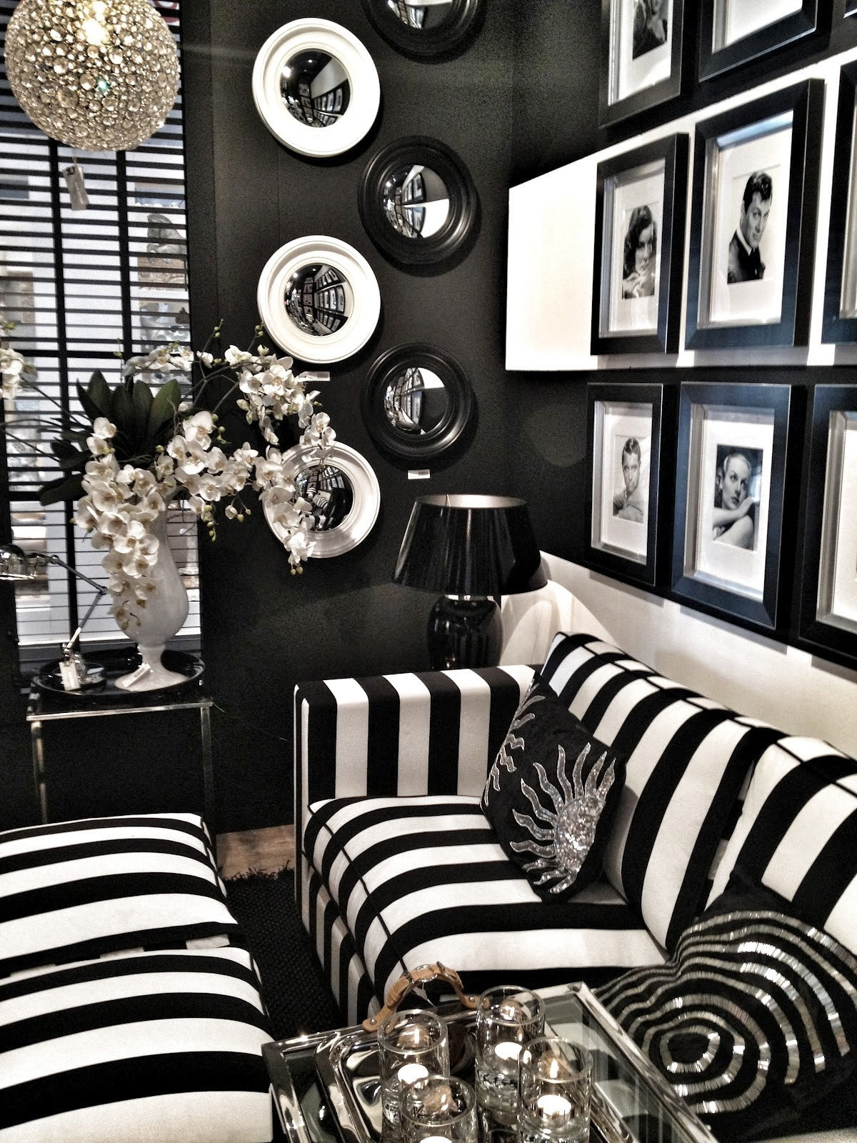 Black and white living room, with striped sofa, and black and white 1940's actor photos on the black walls