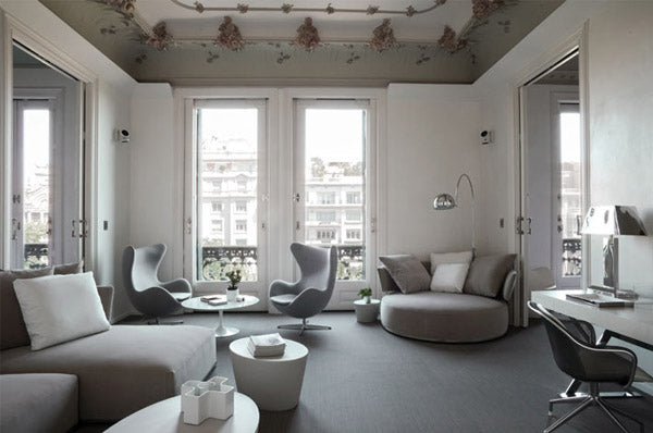 Large living space with light grey chair, snuggle two seater grey chair and light grey swivel chairs around a coffee table