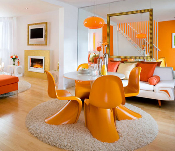 Light wooden floor, white walls, orange staircase wall and orange funky 60s chairs around a white table