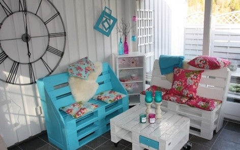 White beach hut style room with chairs made from pallets, one white and the other aqua blue