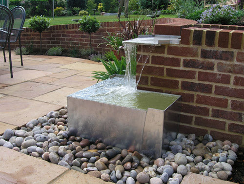Metal garden water feature at the corner of a brick wall, with water falling from on top of the wall