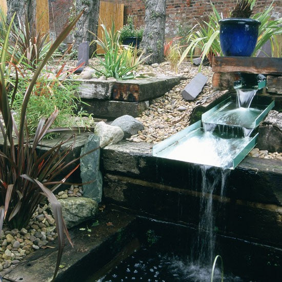 Garden water feature with layered flowing water, dropping into a pond