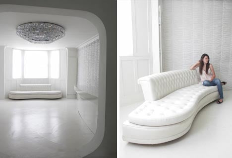 A white living space with long white leather sofa