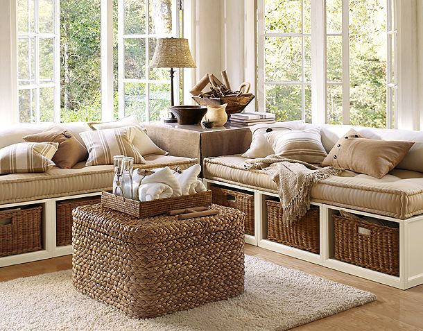 Cream living space with corner window bench, with wicker storage underneath and beige seat pads
