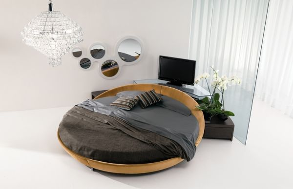 A round bed with black bedding that has rotates and has a TV at the bottom of it