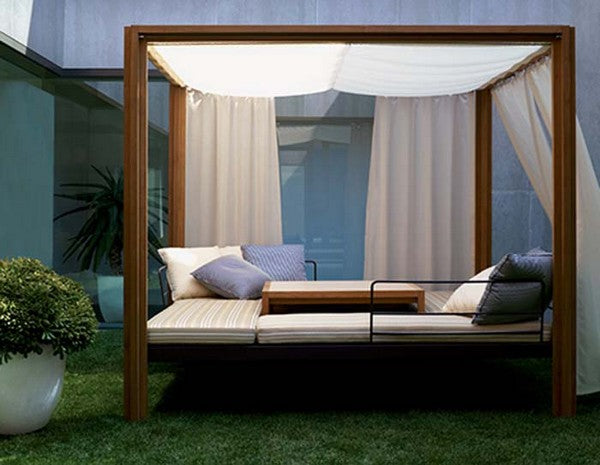 Four poster outdoor day bed with white fabric canopy