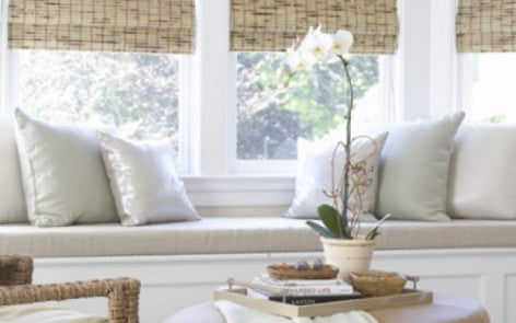 Window seat with cream cushions and bamboo roller blinds in the window