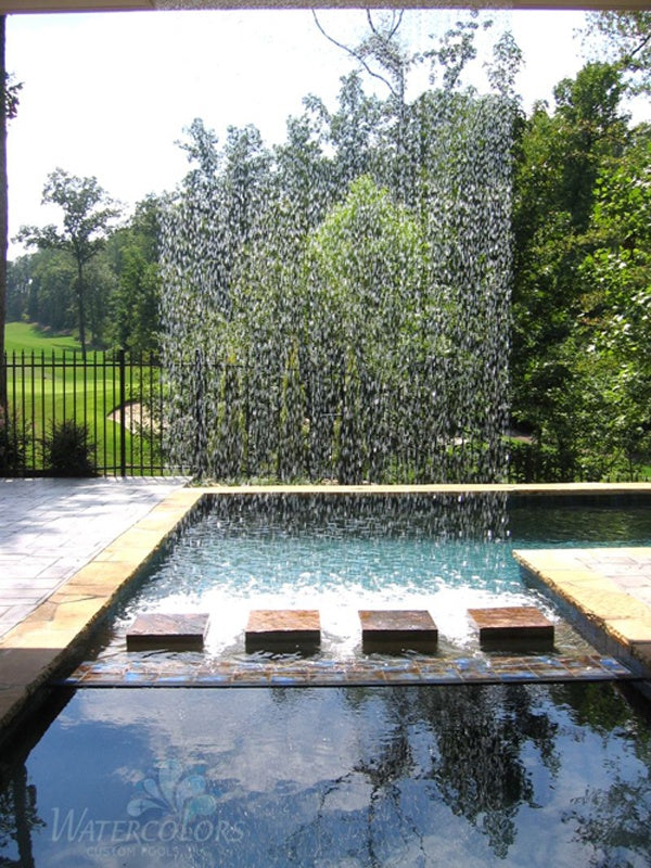 A wall of water falling from above into a large garden water feature