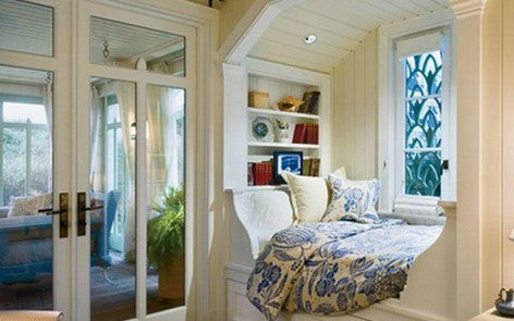 Cream day bed reading nook by a window, next to a conservatory