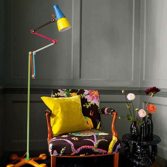 Funky multi-hinged lamp with different arms coloured either green, orange, red, blue, brown, grey or pink, stood above an armchair
