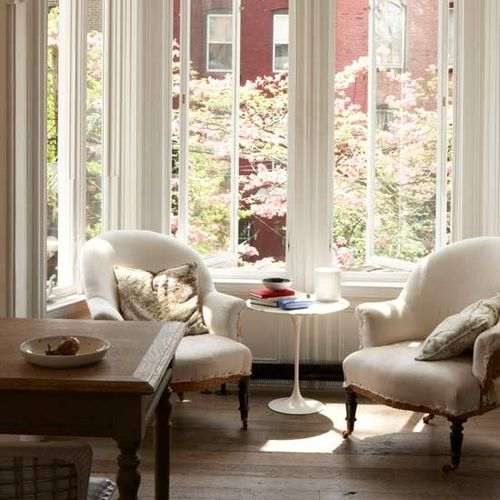 Two arm chairs in front of a large window in a cream living room