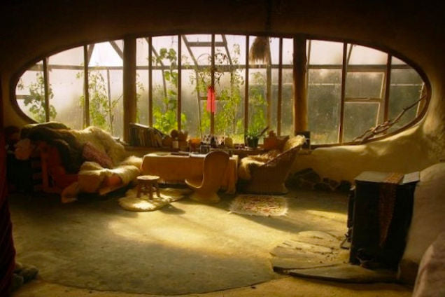 A wide living room window in an oval shape, looking into a green house
