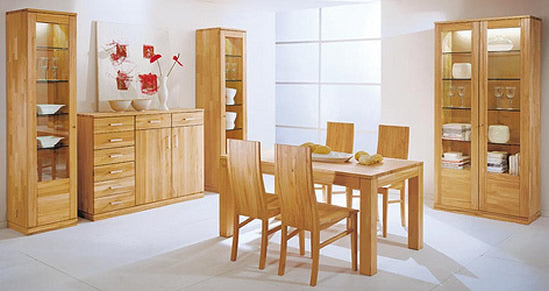 Oak furniture in a white dining room, including table, chairs, drawers and display units