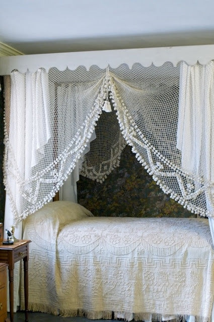 White net curtains creating a canopy around a four poster bed