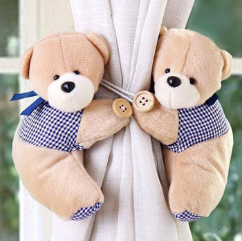 Two teddy bears uses as tiebacks for a pair of curtains