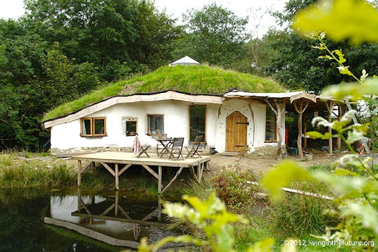 Round white house by a lake, with branches used to create a veranda and the roof covered in grass
