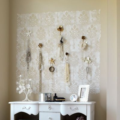 White patterned voile fabric on a wall above a dressing table, with jewellery pinned onto it