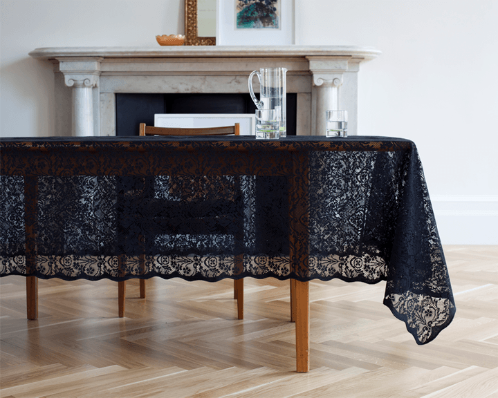 Black lace table cloth on a wooden dining table