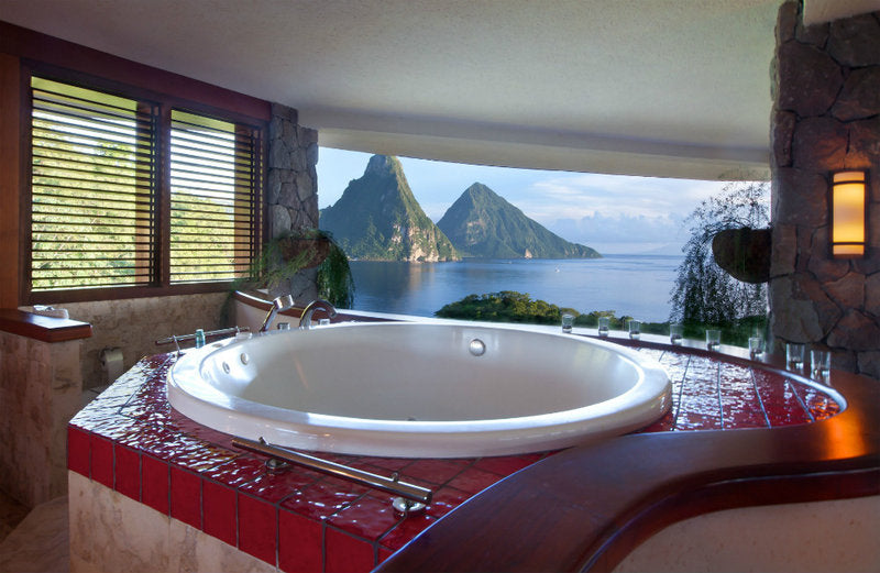 Beige and red tiled bathroom with white round tub overlooking an exotic sea
