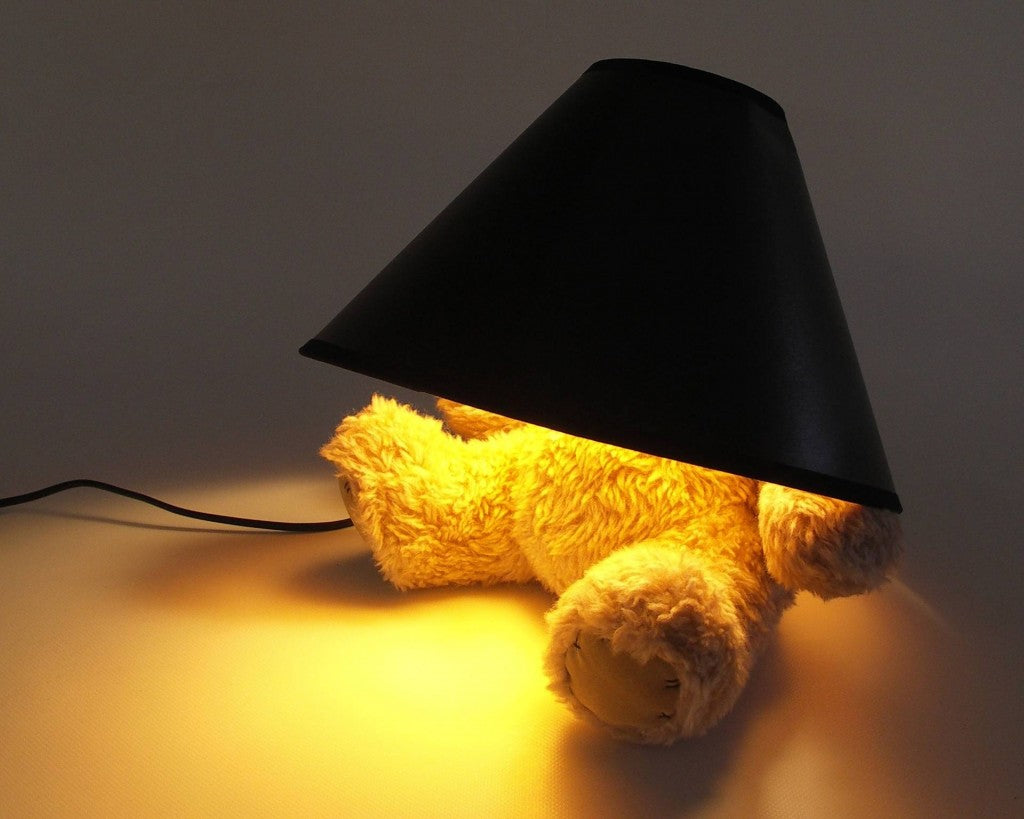 A teddy bear lamp, with lamp shade over its head