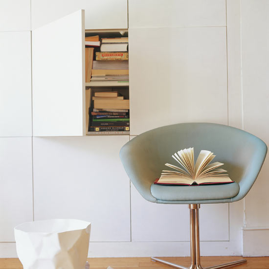 Bookshelves behind a unit door and a duck egg blue reading chair