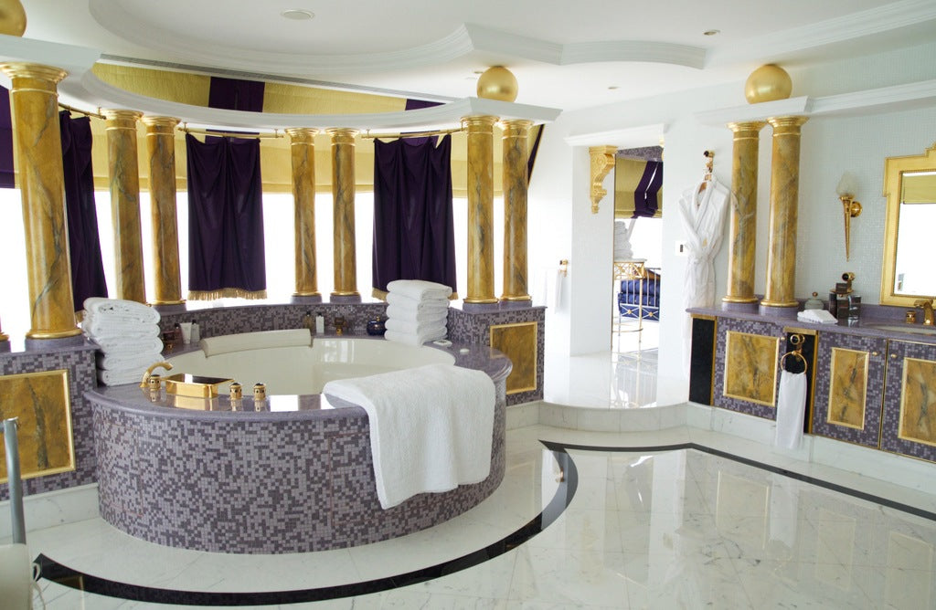 White bathoom with light purple tiles, dark purple privacy curtains and nine gold pillars throughout