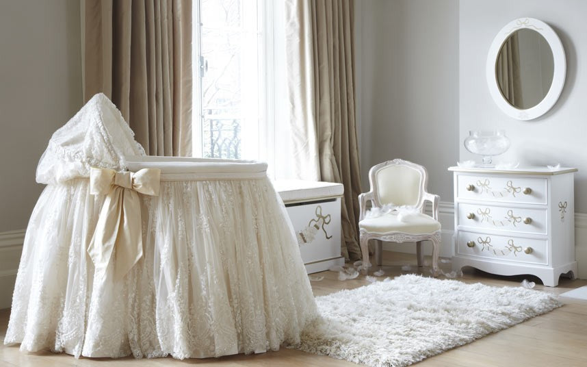 A baby cot with cream lace draped around the outside, trailing to the floor